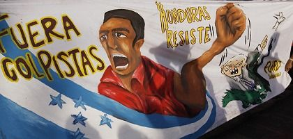 """Fears of a coup epidemic in Latin America: Pro Zelaya protesters hold up a banner reading, """"Coup Leaders Out."""""""