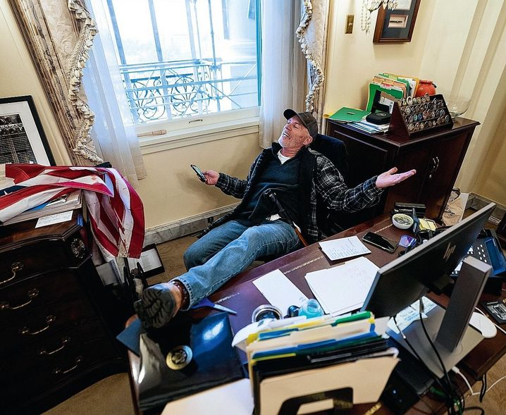 A Trump fan sitting in the chair of Speaker of the House Nancy Pelosi