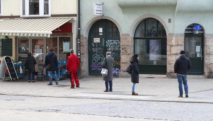 """Vor einem Lebensmittelgeschäft in Jena stehen Kunden in großem Abstand an: """"Der Druck auf die Einzelhändler steigt"""", sagt Christian Gerlitz"""