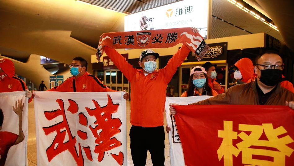 """Fans am Bahnhof von Wuhan: """"Nach mehr als drei Monaten des Herumreisens sind unsere vom Heimweh geplagten Spieler endlich wieder zu Hause"""""""
