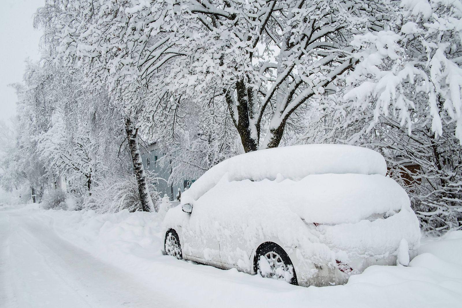 Ein Pkw steht verschneit auf einer Strasse. Leutkirch, Baden Württemberg, Deutschland Neuschnee mit starkem Schneefall