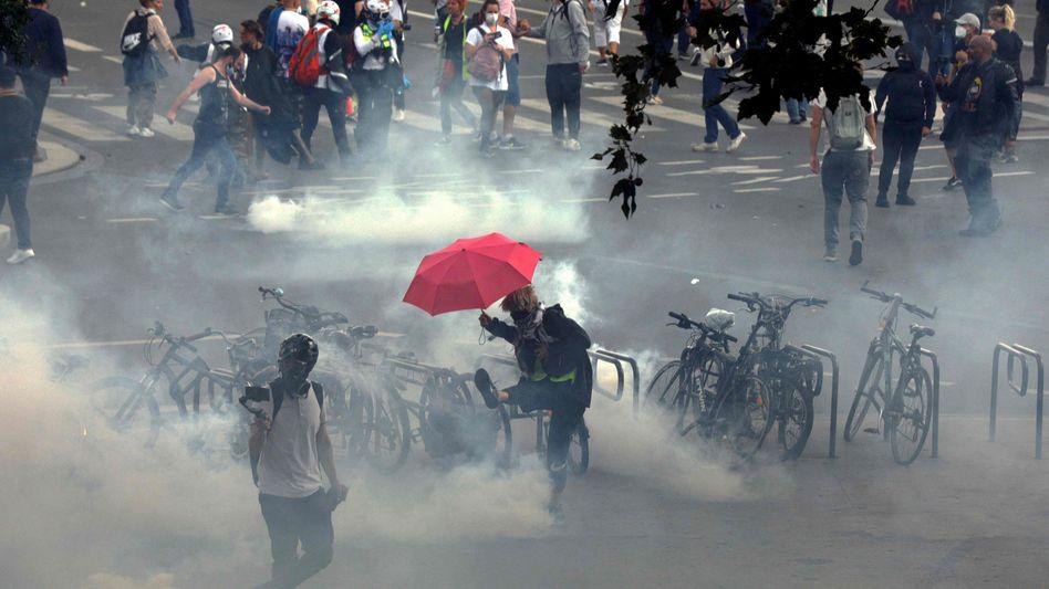Ein Demonstrant in Paris tritt eine Tränengasgranate von sich weg
