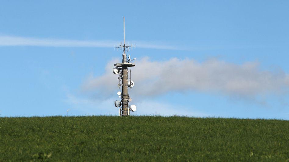 Ein Mobilfunkmast auf einer grünen Wiese. In Deutschland gibt es offenbar noch zu wenige davon