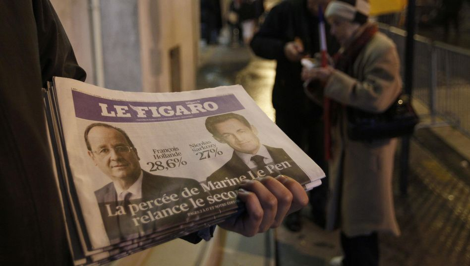 A newspaper seller holds copies of Le Figaro on Sunday evening in Paris.