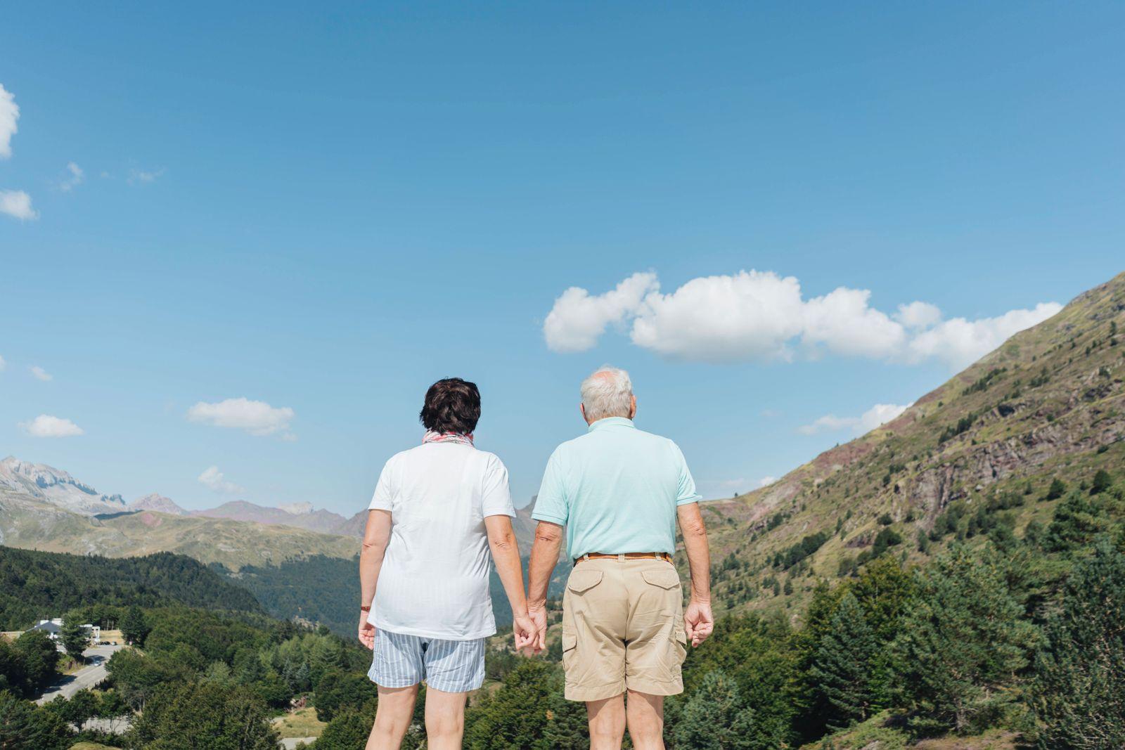 Back view of senior couple looking at view hand in hand, Jaca, Spain model released Symbolfoto PUBLICATIONxINxGERxSUIxAU