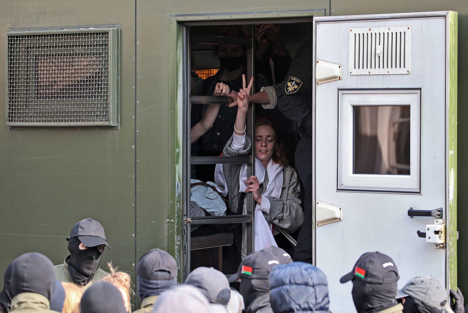 MINSK, BELARUS - SEPTEMBER 12, 2020: A detained protester in a police van gives a V-sign as law enforcement officers de