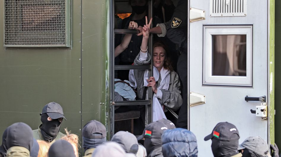 Eine Frau formt nach ihrer Festnahme in Minsk das Peace-Zeichen mit den Fingern
