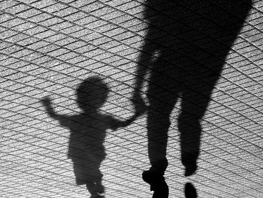 Ein Junge an der Hand seines Vaters