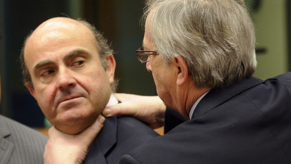 Luxembourg Prime Minister Jean-Claude Juncker (right) with Spain's Economy Minister Luis de Guindos at the finance ministers' meeting on Monday: Despite recent progress, the euro crisis isn't over yet.