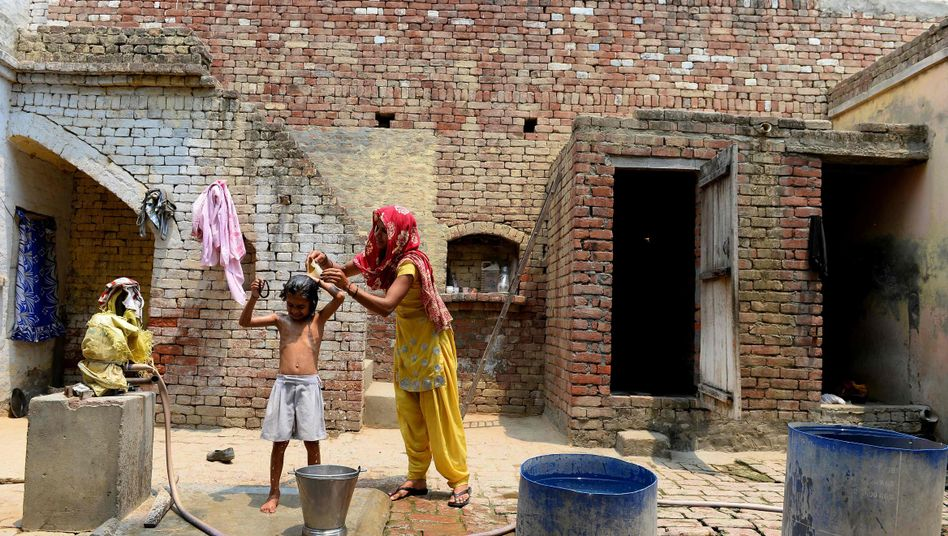 A woman bathes her daughter in a village in Uttar Pradesh