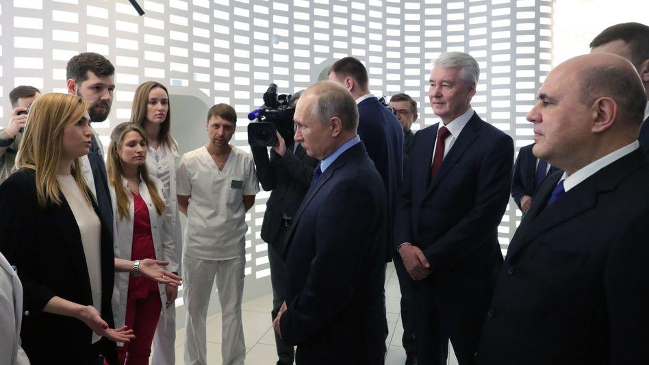 Putin (M.) mit Moskaus Bürgermeister Sergei Sobyanin (2.r.) und Premierminister Michail Mischustin (r.) im Moskauer Corona-Lagezentrum: Politik und Infektionskrankheit entwickeln eine Wechselwirkung.