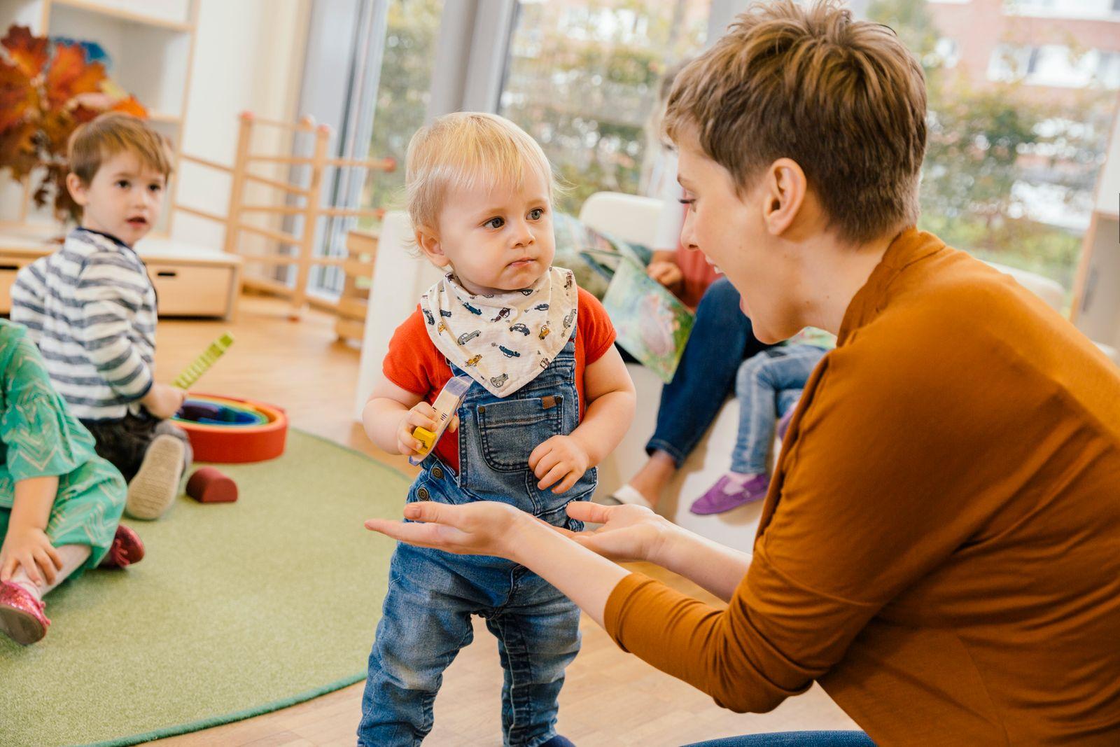 Pre-school teacher playing with little boy in kindergarten