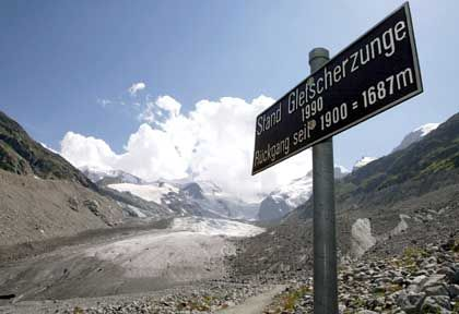 "Alpine glaciers are melting rapidly. The sign reads, ""Extent of glacier tongue in 1990."" The photo was taken in 2003."