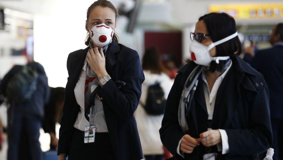 """Passanten mit Atemschutzmasken am Flughafen Rom: Auswirkungen bereits """"deutlich zu spüren"""""""