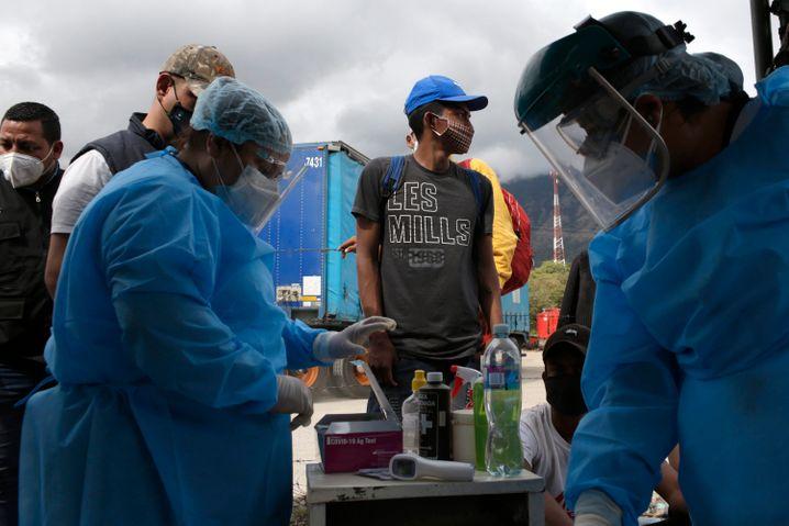 Mitarbeiter eines mobilen Gesundheitszentrums testen Migranten in Honduras auf Coronainfektionen