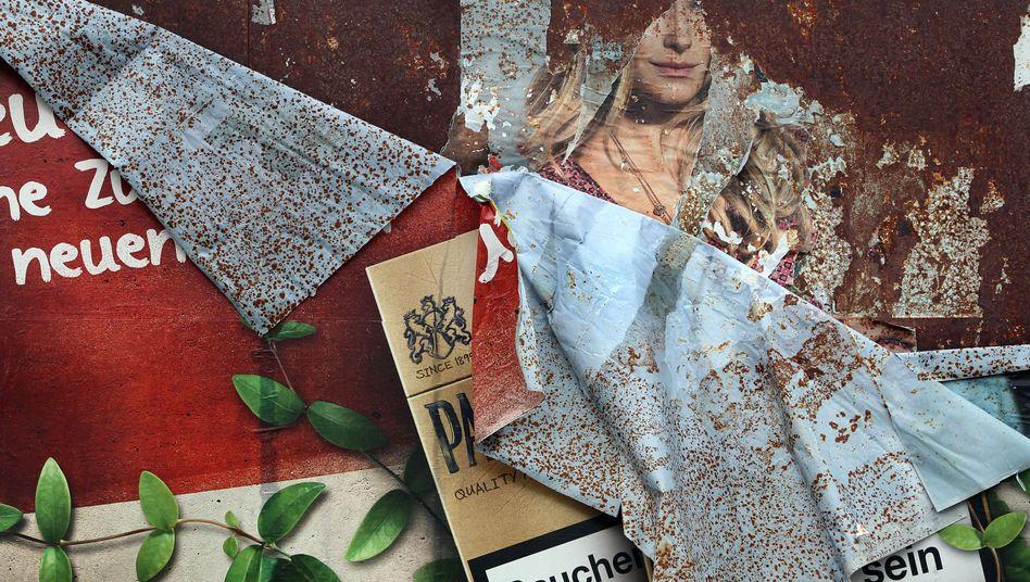 Ein Plakat mit Zigarettenwerbung löst sich von einer Werbewand