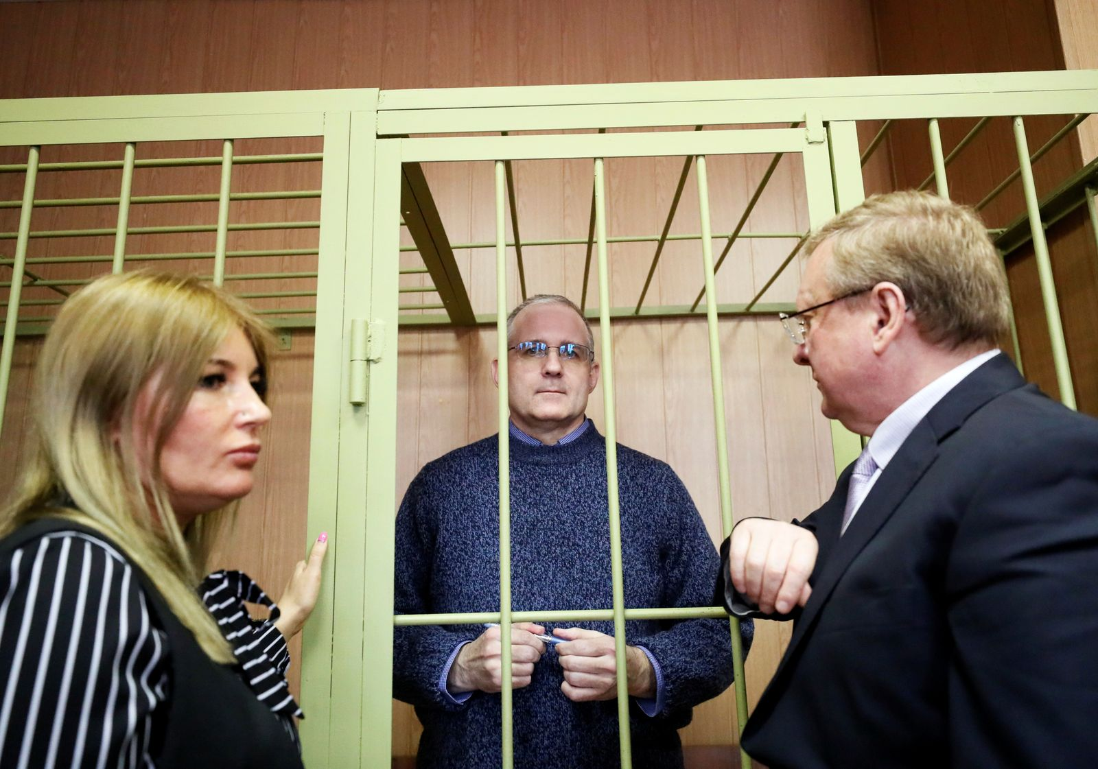 Former U.S. marine Paul Whelan who is being held on suspicion of spying talks with his lawyers Vladimir Zherebenkov and Olga Kralova, as he stands in the courtroom cage after a ruling regarding extension of his detention, in Moscow