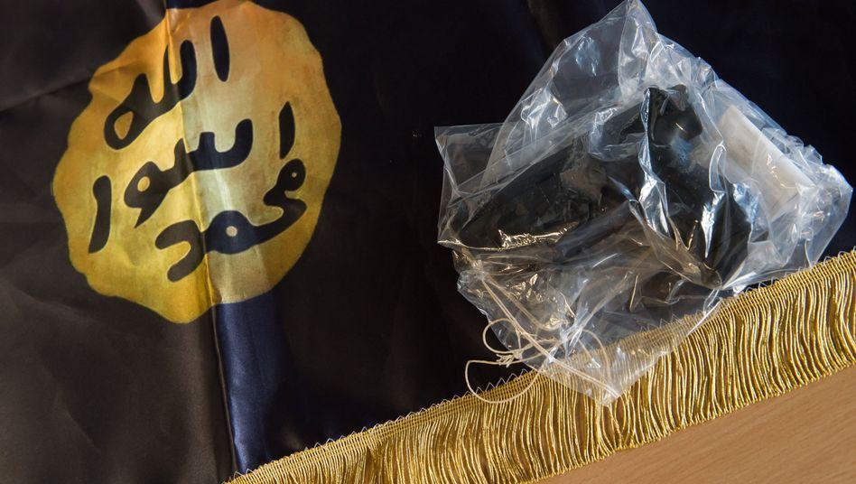 Bei Razzia gegen Salafisten beschlagnahmte IS-Fahne und Waffe (Archiv)