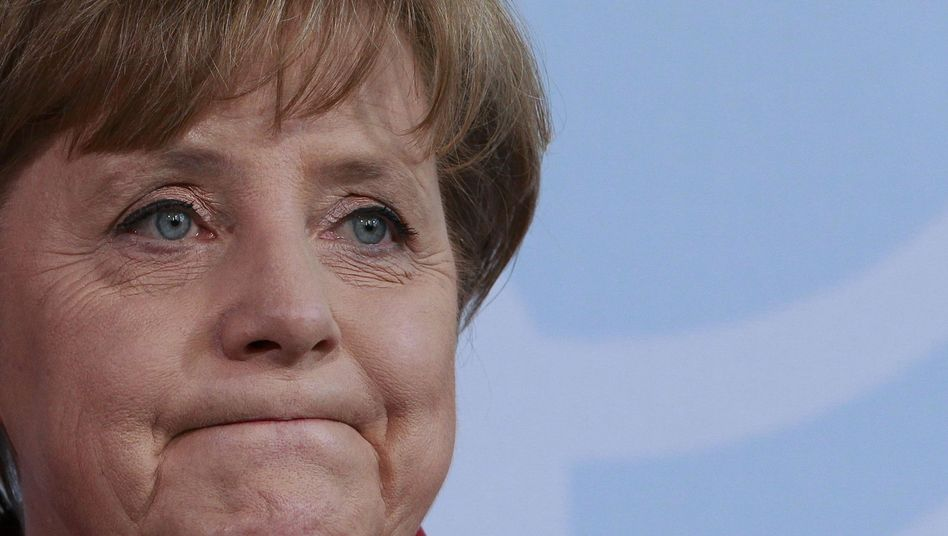Looking worried: Chancellor Angela Merkel facing the press on Tuesday.