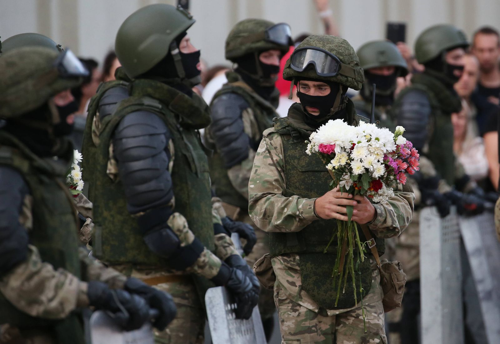 MINSK, BELARUS - AUGUST 14, 2020: A Belarusian law enforcement officer holds flowers during a protest against the resul