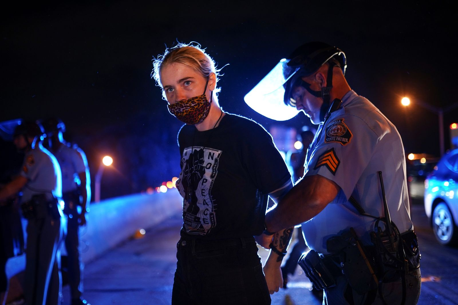 Police detain a protester for blocking traffic during a rally against racial inequality and the police shooting death of Rayshard Brooks, in Atlanta