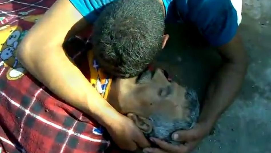 A video image purports to show a man mourning a victim of attacks in Tremseh, Syria.