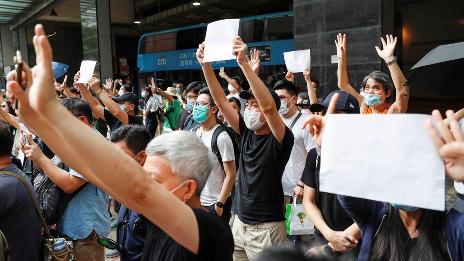 Demonstranten halten weißes Papier hoch, um gegen das Verbieten von Slogans zu protestieren