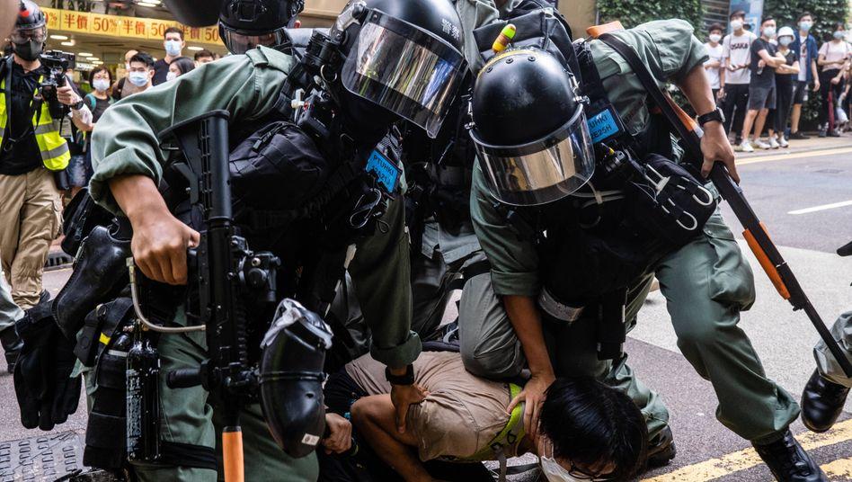 Chinesische Übermacht: Ein Demonstrant wird von Sicherheitskräften in Hongkong auf den Boden gedrückt