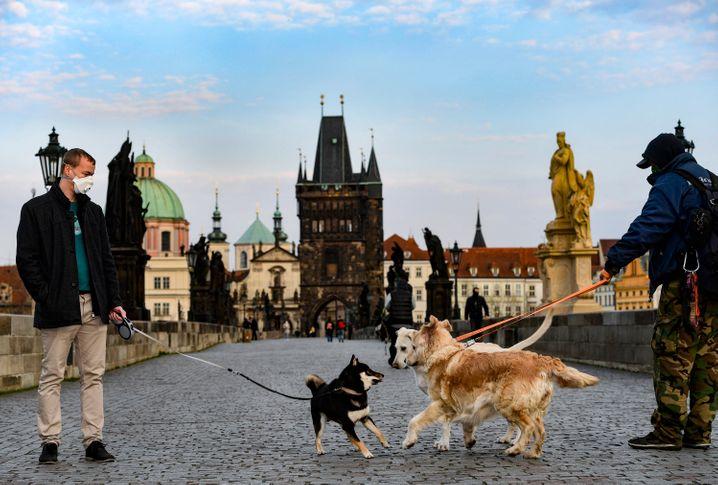 Zwei Männer mit Hunden auf der Karlsbrücke in Prag