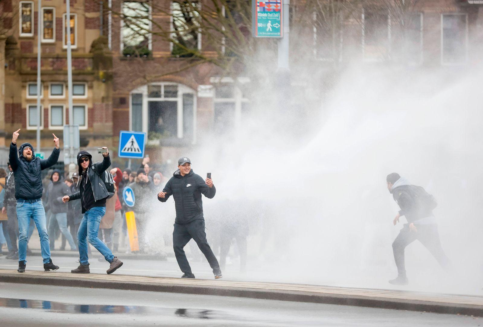 AMSTERDAM - De politie heeft een waterkanon ingezet om demonstranten te weren van het Museumplein, waar zij zich hadden