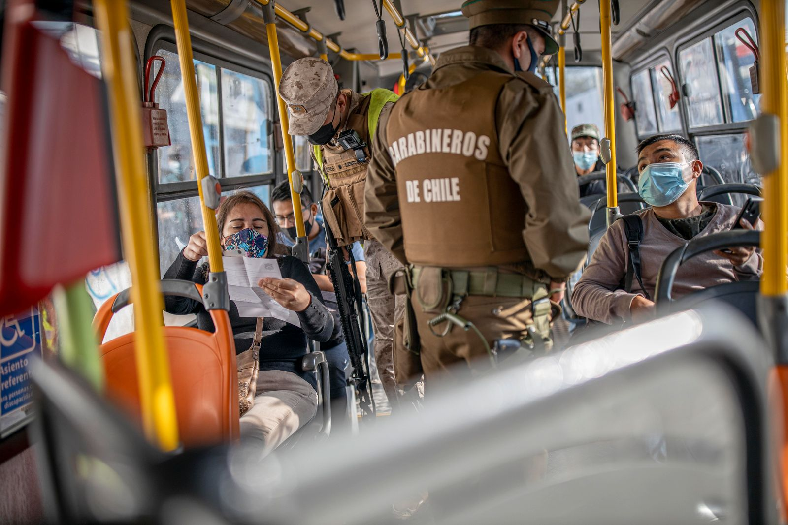 A solider and a carabineros verify the health permits of the