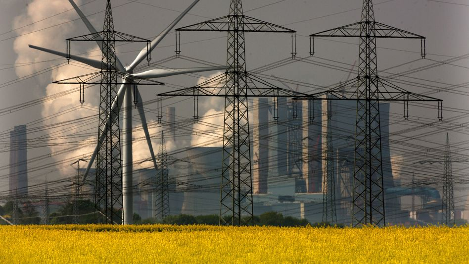 Rapeseed for biofuels and wind generators for clean electricity -- against a backdrop of a coal-fired power station in Germany.
