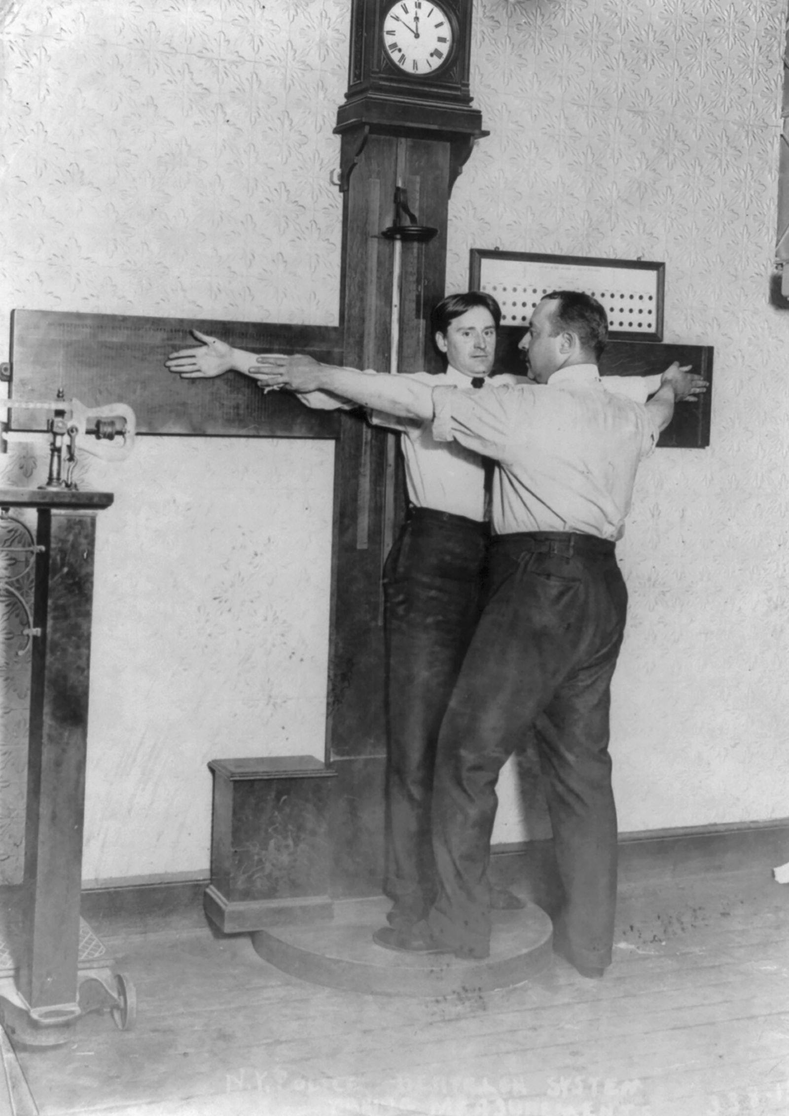 Forensik - New York City Police Dept. activities: taking Bertillon measurements--armspan