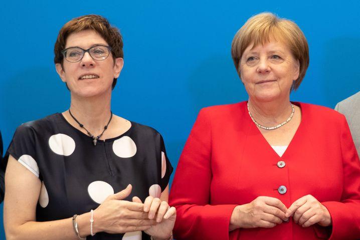 """Kramp-Karrenbauer und Merkel: Die Aufteilung auf eine Politikerin als Kanzlerin und eine andere Politikerin als Parteichefin sei """"für die CDU ja wirklich auch ein Experiment, das fordert uns alle"""", so AKK."""