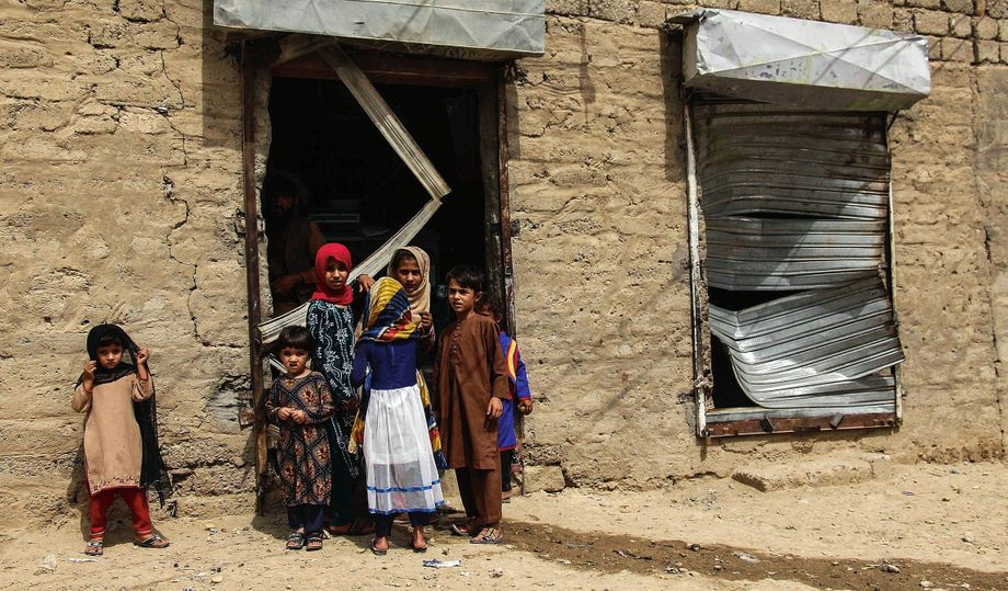 Children stand in front of a bombed-out business in Kandahar: At night, the streets belong to the Taliban.