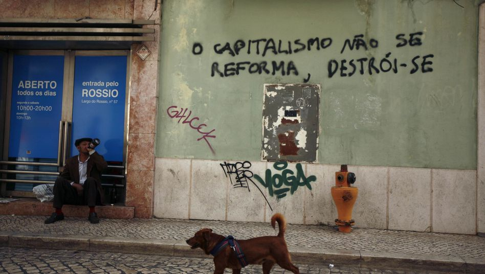 "A man in Lisbon next to graffiti reading ""capitalism doesn't reform and must be destroyed."" An agreement was reached on a €78 billion bailout package for Portugal on Wednesday."