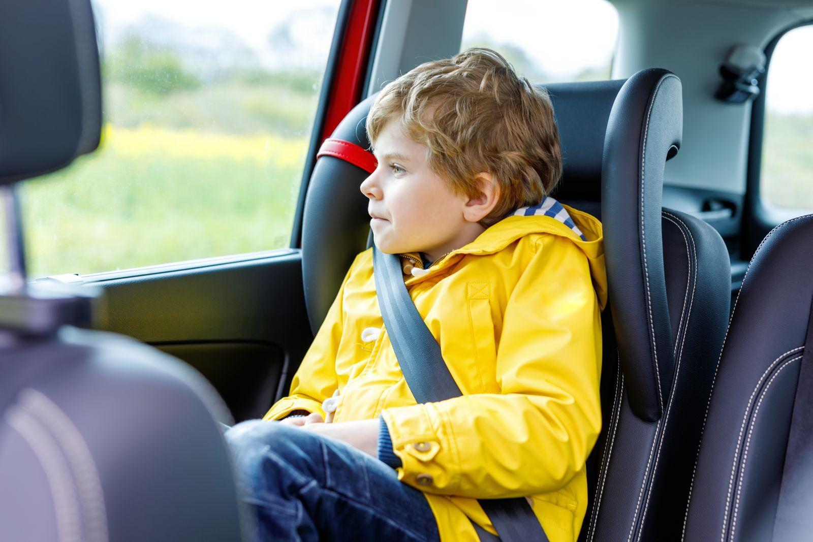 Adorable cute preschool kid boy sitting in car in yellow rain coat.