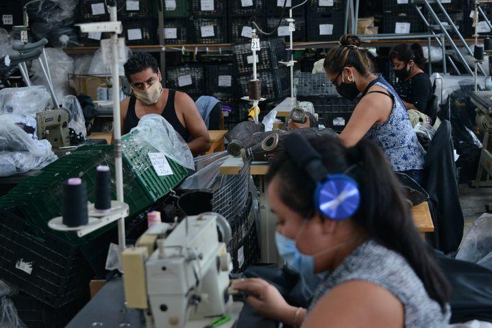In einer Fabrik nähen Arbeiterinnen und Arbeiter Schutzmasken – sie selbst sind oft schlecht geschützt