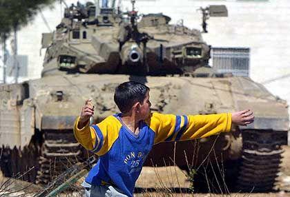 Wut und Hass auf den Nachhauseweg: Ein palästinensischer Junge bewirft einen israelischen Panzer mit Steinen
