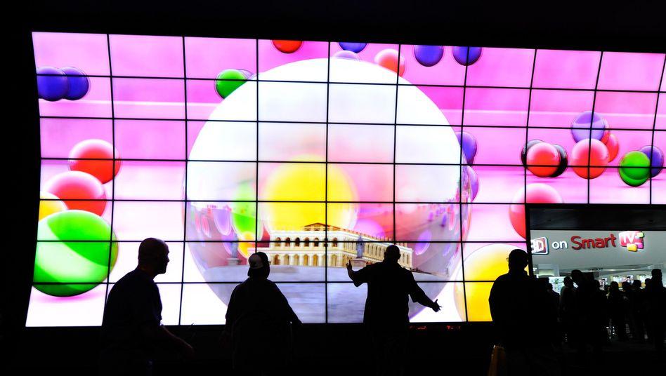 Messebesucher auf der CES vor einer Wand aus Smart-TVs
