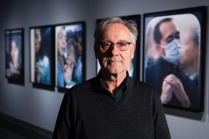 """Michael Wolf vor Bildern der Serie """"Toyko Compression"""""""