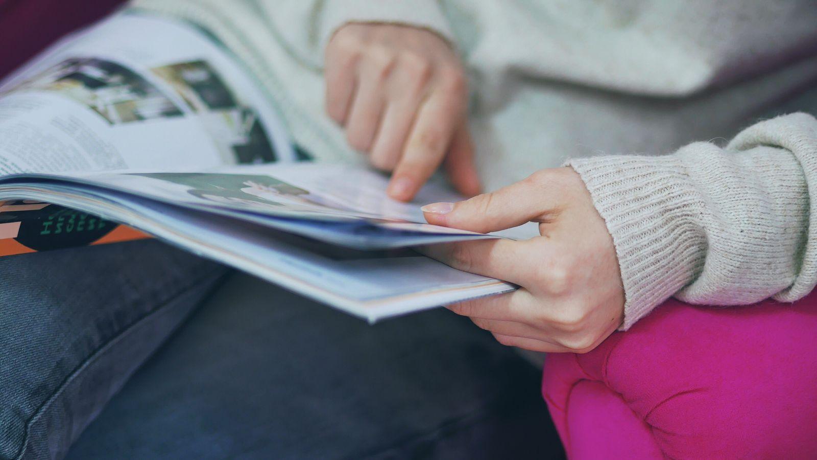 EINMALIGE VERWENDUNG Lesende Person/ Closeup/ Zeitschrift/ Symbolbild