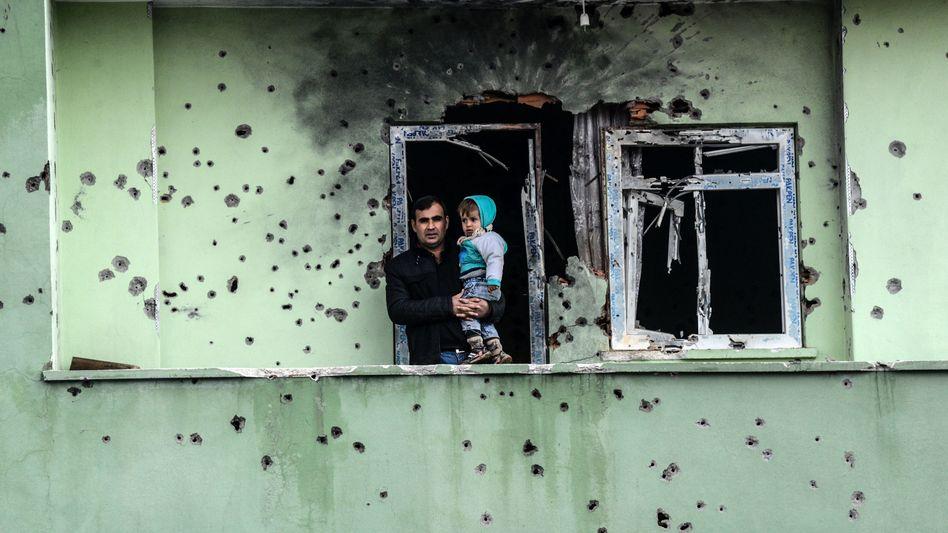Mann und Kleinkind auf einem Balkon in der Stadt Silopi im Südosten der Türkei