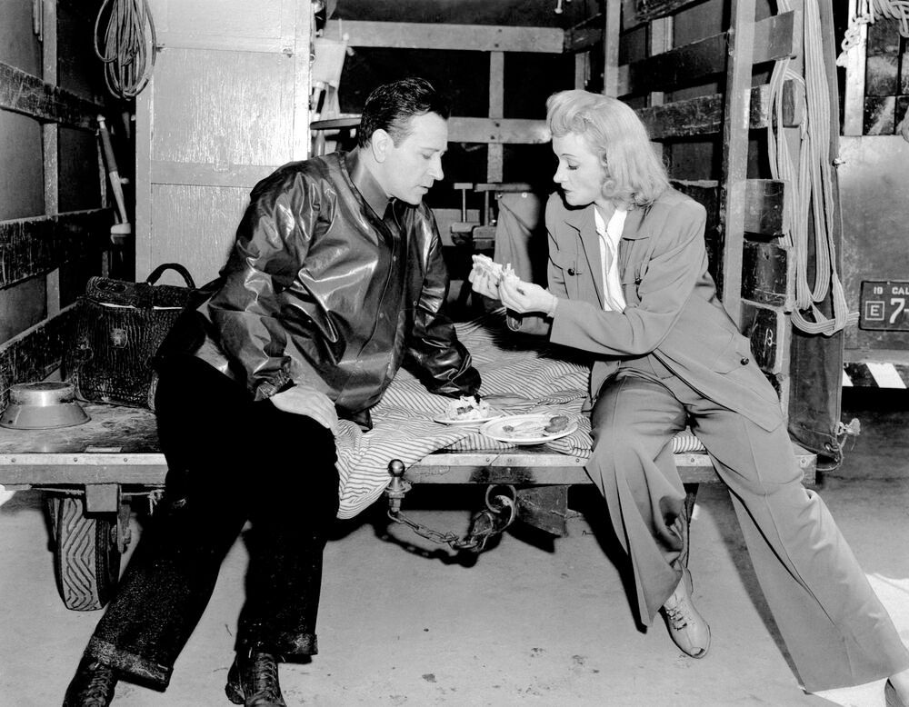 MANPOWER, from left, George Raft, Marlene Dietrich, sharing a sandwich on-set, 1941 Courtesy Everett Collection PUBLICAT