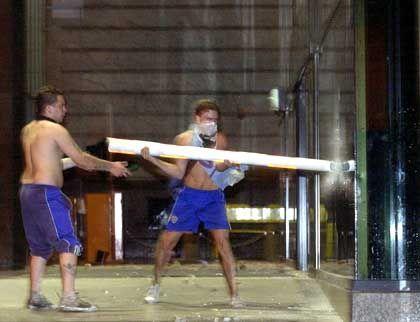 Auch die Ausrufung des Ausnahmezustandes konnte Buenos Aires nicht befrieden. Überall kommt es zum Ausbruch von Gewalt. Diese beiden Männer versuchen das Fenster einer Bank zu zertrümmern.