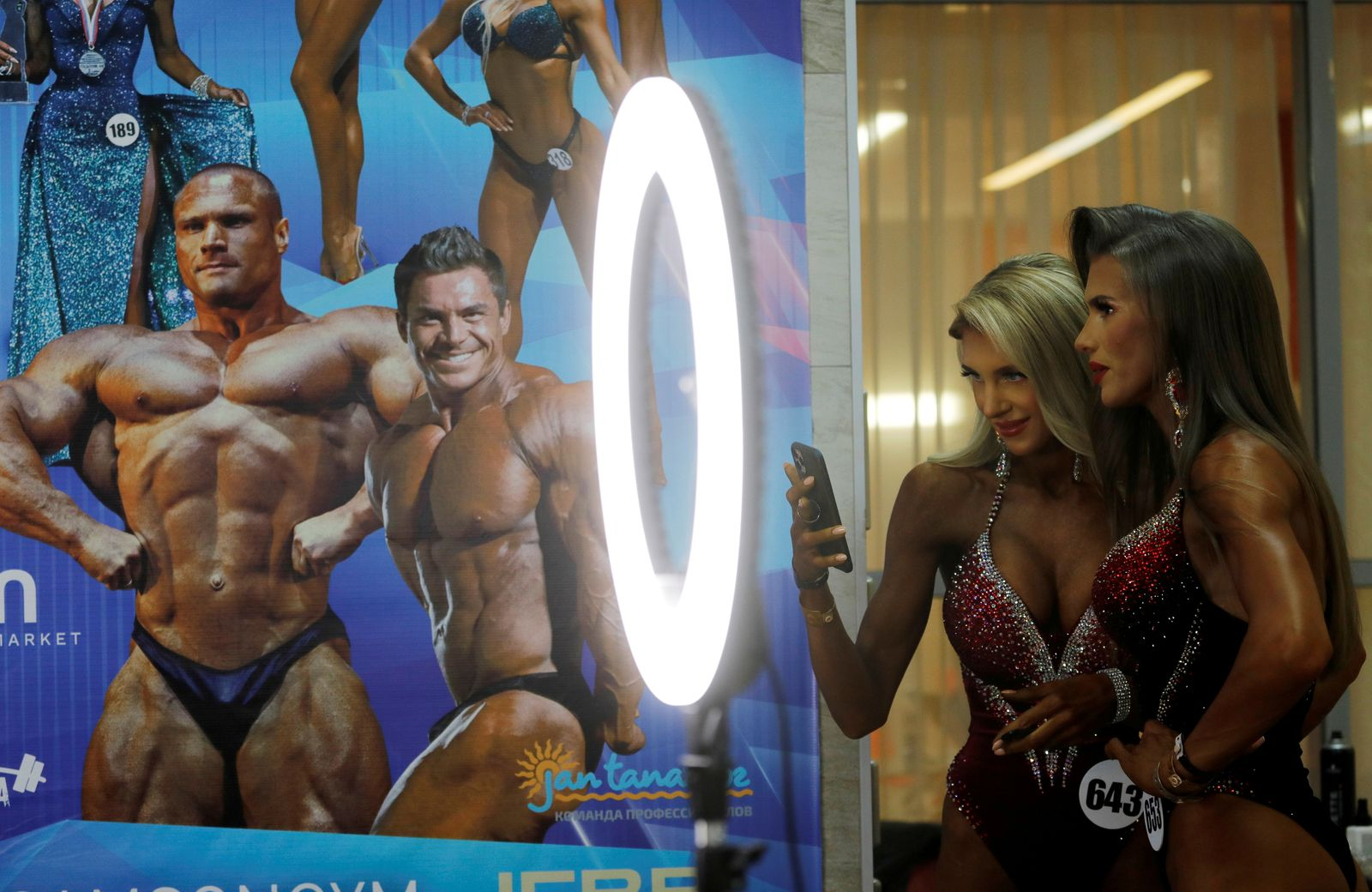 Participants take pictures backstage during a local bodybuilding championship in Krasnodar