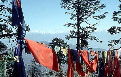 Blick vom Pass Dochu La: Gebetsfahnen vor schneebedecktem Himalaja-Panorama