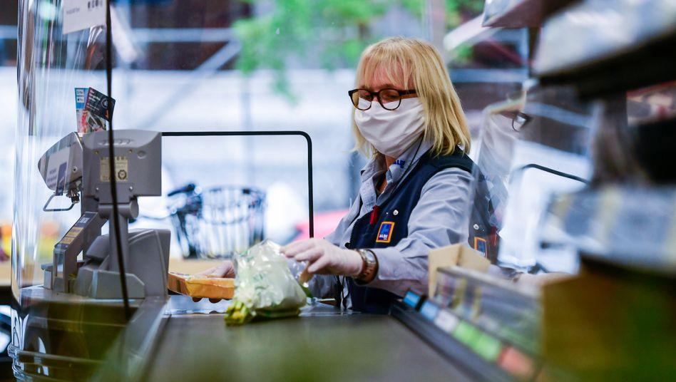 Supermarktkassiererin hinter einem sogenannten Spuckschutz