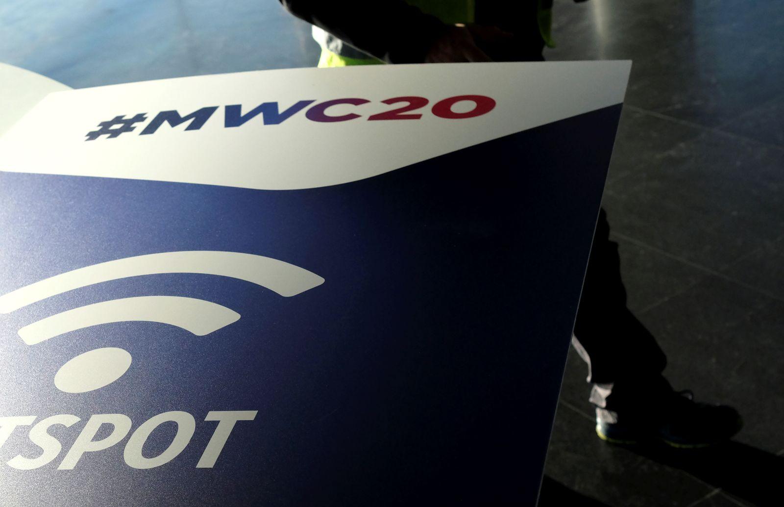 An employee walks past an MWC20 banner in Barcelona