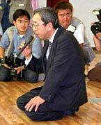 Noch einmal der zerknirschte Kitani, vor Evakuierten auf dem Boden sitzend